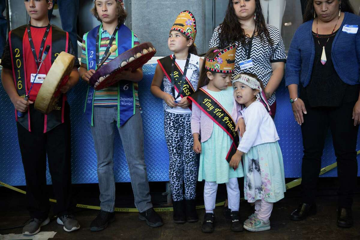 Sisters Taylor Ives, 5, and Charlotte Ives, young members of the Suquamish Tribe, lean on one another while performing a song during the keel-laying ceremony for Washington State Ferries' newest vessel under construction, the Suquamish, in a warehouse at Vigor's Harbor Island Shipyard, Tuesday, May 10, 2016.
