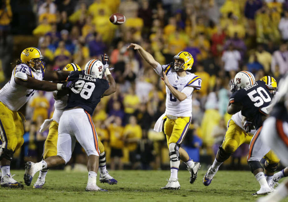 LSU quarterback Zach Mettenberger (8) passes between Auburn defensive back Adam Dyas (38) and defensive tackle Ben Bradley (50) in the second half of an NCAA college football game in Baton Rouge, La., Saturday, Sept. 21, 2013. LSU won 35-21. (AP Photo/Gerald Herbert) Photo: Gerald Herbert
