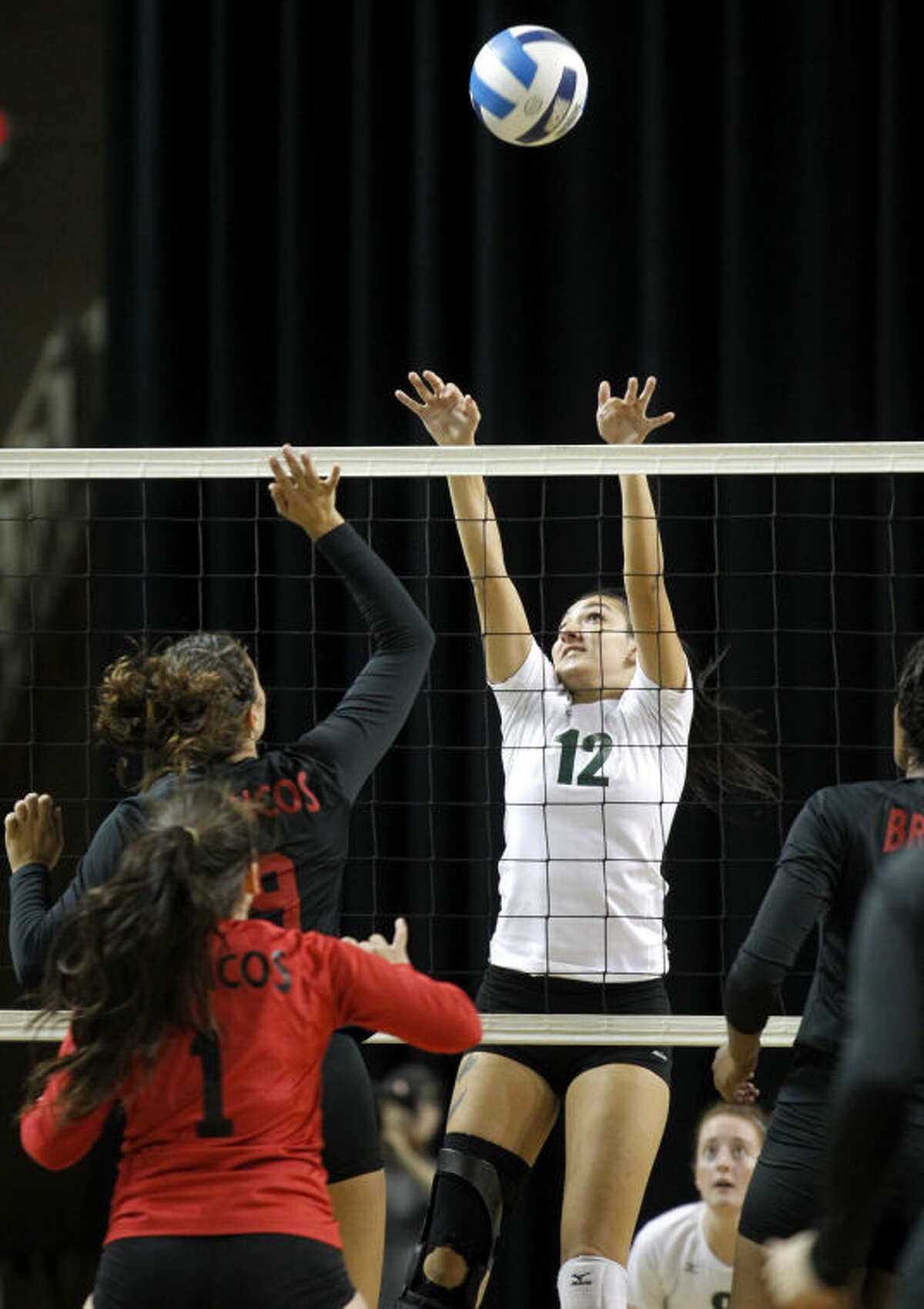 Midland College's Megan Sanchez blocks a hit from New Mexico's Veronica Baric on Wednesday at Chaparral Center. James Durbin/Reporter-Telegram