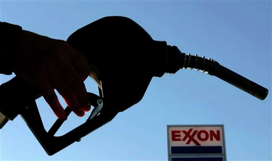 """FILE - In this Wednesday, Oct. 26, 2005, file photo, drivers fill up at an Exxon gas station, in Richardson, Texas. Exxon Mobil Corp. said Friday, Sept. 28, 2013, that it will begin offering benefits to legally married same-sex couples in the U.S. for the first time starting the first week of October 2013. The company says it will recognize """"all legal marriages"""" when it determines eligibility for health care plans for the company's 77,000 employees and retirees in the U.S. (AP Photo/Matt Slocum, File) Photo: Matt Slocum / AP"""