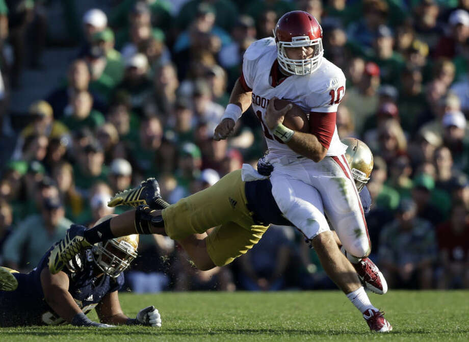 Oklahoma's Blake Bell (10) runs out of the tackle of Notre Dame 's Dan Fox during the second half of an NCAA college football game on Saturday, Sept. 28, 2013, in South Bend, Ind. Oklahoma defeated Notre Dame 35-21. (AP Photo/Darron Cummings) Photo: Darron Cummings