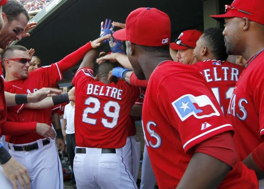 Texas Rangers' Adrian Beltre (29) is congratulated in the dugout after his solo home run that came off a pitch from Los Angeles Angels relief pitcher Ernesto Frieri (49) in the eighth inning Sunday in Arlington. The Rangers won 6-2. (AP Photo/Tony Gutierrez) Photo: Tony Gutierrez