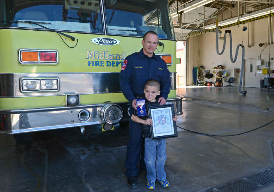 MFD Capt. Bryan Chatwell and his 7-year-old son Carson stand with an Act of Valor certificate and medal Saturday in the Station 3 garage. Chatwell received the award for acting to assist a diabetic man in June. James Durbin/Reporter-Telegram Photo: JAMES DURBIN