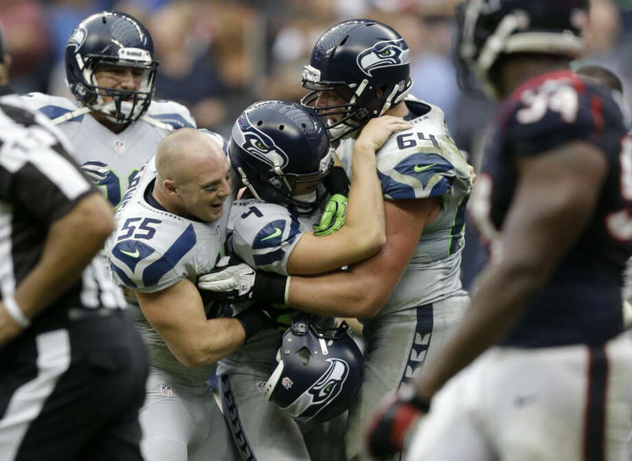 Seattle Seahawks' Steven Hauschka (4) is congratulated by teammates Heath Farwell (55) and J.R. Sweezy (64) after kicking the winning field goal against the Houston Texans during overtime on Sunday in Houston. Seattle won 23-20. (AP Photo/Patric Schneider) Photo: Patric Schneider
