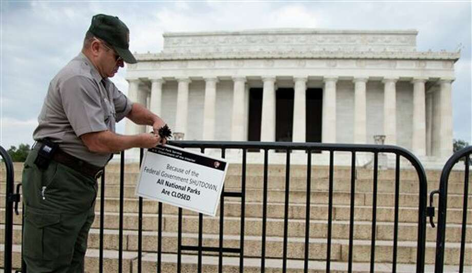 A National Park Service employee posts a sign on a barricade to close access to the Lincoln Memorial in Washington, Tuesday, Oct. 1, 2013. Congress plunged the nation into a partial government shutdown Tuesday as a long-running dispute over President Barack Obama's health care law stalled a temporary funding bill, forcing about 800, 000 federal workers off the job and suspending most non-essential federal programs and services. (AP Photo/Carolyn Kaster) Photo: Carolyn Kaster / AP