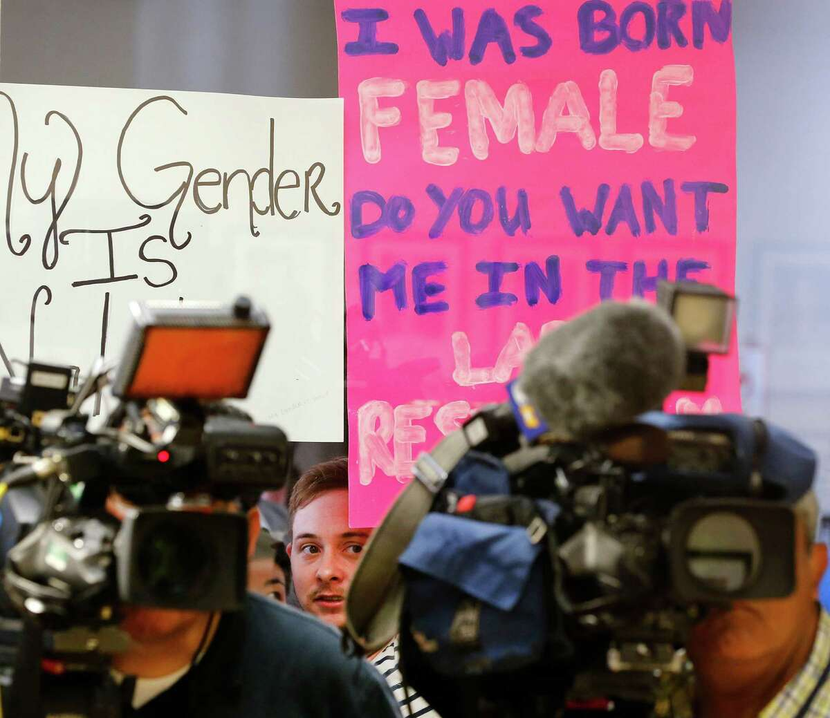 Protestors hold up signs to the window outside a room where Lt. Gov. Dan Patrick addresses the media on Fort Worth Superintendent Kent Scribner's policy to allow transgender students comfortable access to bathrooms. The press conference held before the school board meeting was at the Fort Worth ISD Board of Education complex in Fort Worth, Tuesday, May 10, 2016. (Tom Fox/The Dallas Morning News)