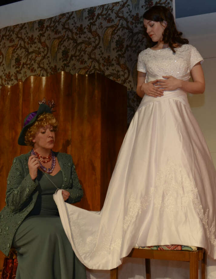 Samatha Spencer as Judy tries on her wedding dress as Kristin Robbins playing Daphne hems the bottom in MCT's production of Perfect Wedding. Tim Fischer\Reporter-Telegram Photo: Tim Fischer