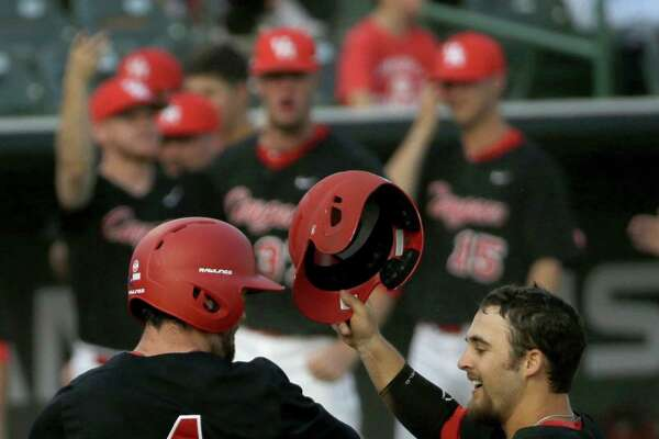 University of Houston Zac Taylor, left, and Michael Pyeatt, right, celebrate scoring against Rice University during the fourth inning of baseball game in Reckling Park at Rice Tuesday, May 10, 2016, in Houston.