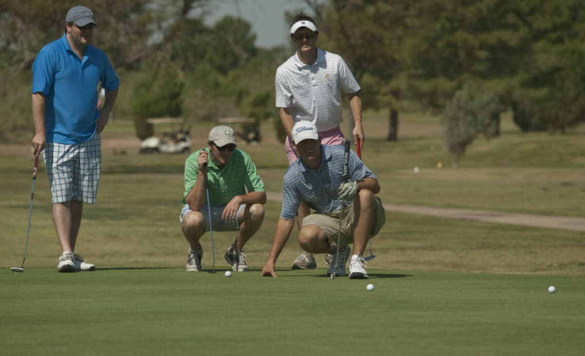 Kelly Strickling and Kyle Davis squat down to check the line on their putt as John Clifton and Mitchell Strickling lookon Saturday during the Permian Basin Area Foundation Golf to Honor Tournament benefiting the Patrick Wayland Memorial Scholarship Fund. Tim Fischer\Reporter-Telegram