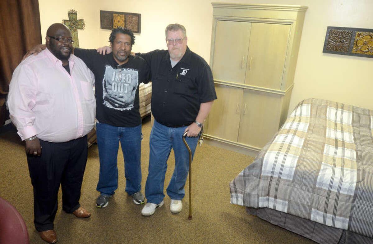 From left, Tyrone McGruder, senior support supervisor, Luis Antonio Diaz, New Direction resident, and Kevin Egan, facility supervisor, pose for a picture in a room at the New Direction Ministry building on Wednesday. James Durbin/Reporter-Telegram