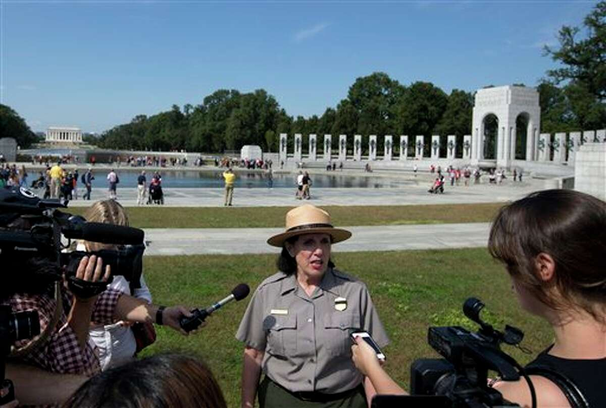 National Park Service spokeswoman Carol Johnson speaks to reporters at the National World War II Memorial in Washington, Tuesday, Oct. 1, 2013. A group of veterans walked past barriers at the closed World War II memorial with help from members of Congress. Hundreds of veterans arrived for a previously scheduled visit to the memorial Tuesday morning to find it barricaded by the National Park Service. Members of Congress, including Republican Rep. Michele Bachmann of Minnesota, went to the site after receiving panicked emails and cut police tape to let in the veterans from Iowa and Mississippi. (AP Photo/Carolyn Kaster)