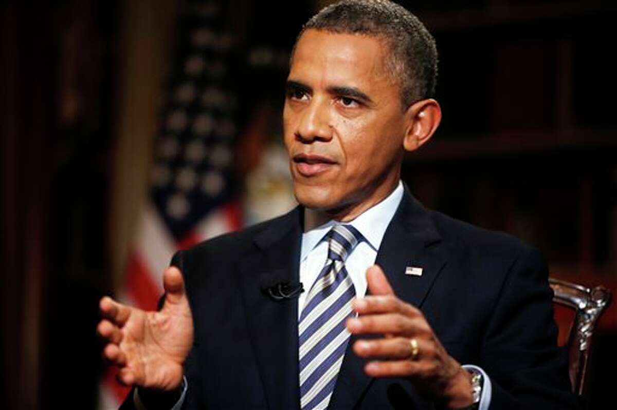 In this photo taken Friday, Oct. 4, 2013, President Barack Obama speaks during an exclusive interview with The Associated Press in the White House library in Washington. Defending the shaky rollout of his health care law, Obama said frustrated Americans