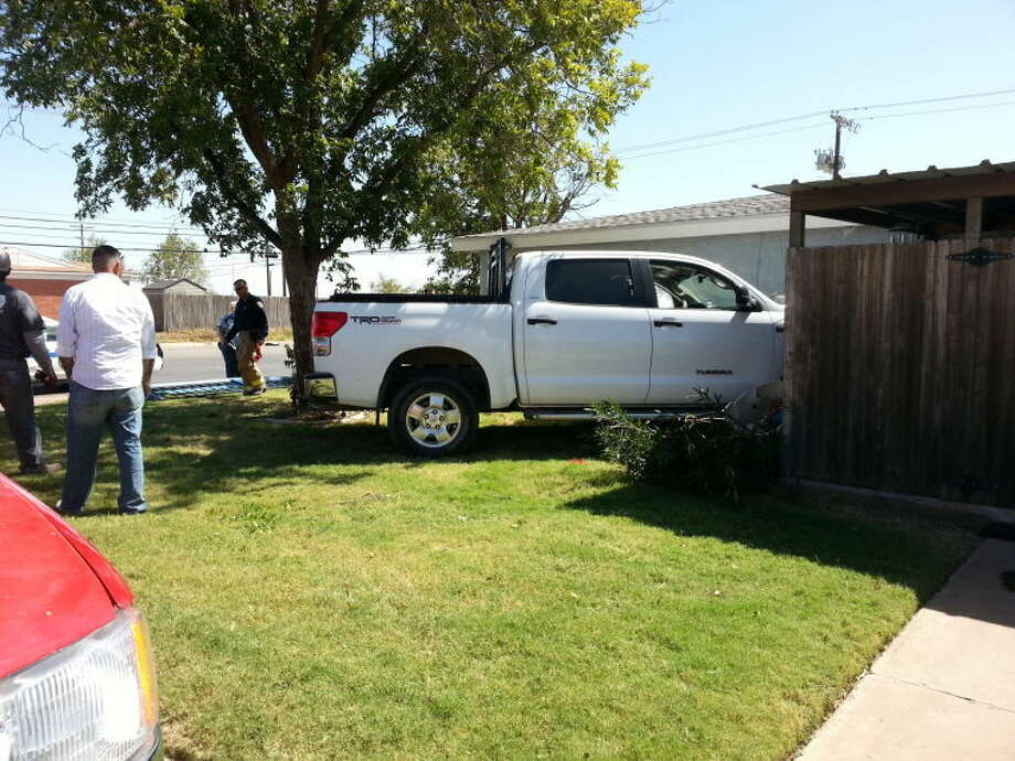 A wrecker removes a pickup from the fenced-in patio area of a southwest Midland home Saturday at about 1:30 p.m. The pickup veered across the property after nearly colliding with another driver who ran a stop sign at the intersection of Anetta and Midland drives.