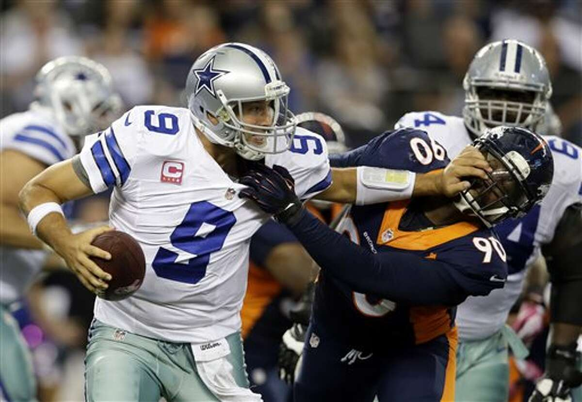 Dallas Cowboys quarterback Tony Romo (9) attempts to fight off a sack by Denver Broncos' Shaun Phillips (90) late in the fourth quarter of an NFL football game Sunday in Arlington. The Broncos won 51-48. (AP Photo/Tony Gutierrez)