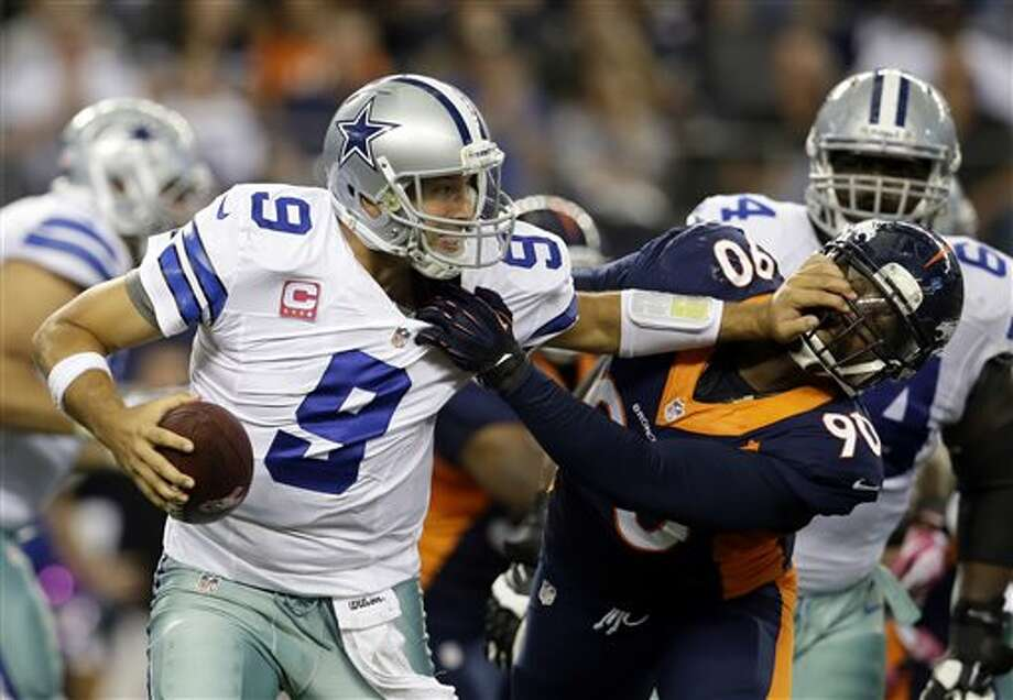 Dallas Cowboys quarterback Tony Romo (9) attempts to fight off a sack by Denver Broncos' Shaun Phillips (90) late in the fourth quarter of an NFL football game Sunday in Arlington. The Broncos won 51-48. (AP Photo/Tony Gutierrez) Photo: Tony Gutierrez / AP