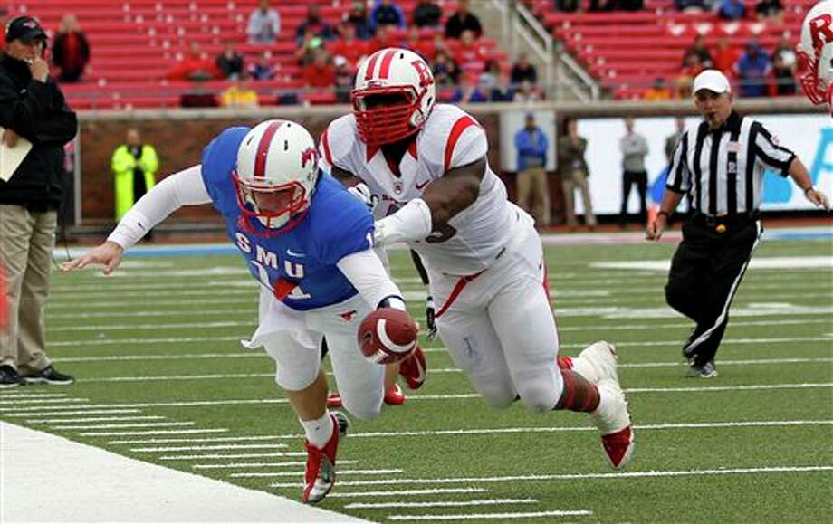 SMU quarterback Garrett Gilbert is forced out-of-bounds by Rutgers defensive end Marcus Thompson during the second overtime period of an NCAA football game against SMU at Gerald J. Ford Stadium in Dallas, Saturday, Oct. 5, 2013. Rutgers defeated SMU 55-52 in triple overtime. (AP Photo/The Dallas Morning News, Mike Stone) MANDATORY CREDIT; MAGS OUT; TV OUT; INTERNET USE BY AP MEMBERS ONLY; NO SALES Photo: Mike Stone / The Dallas Morning News