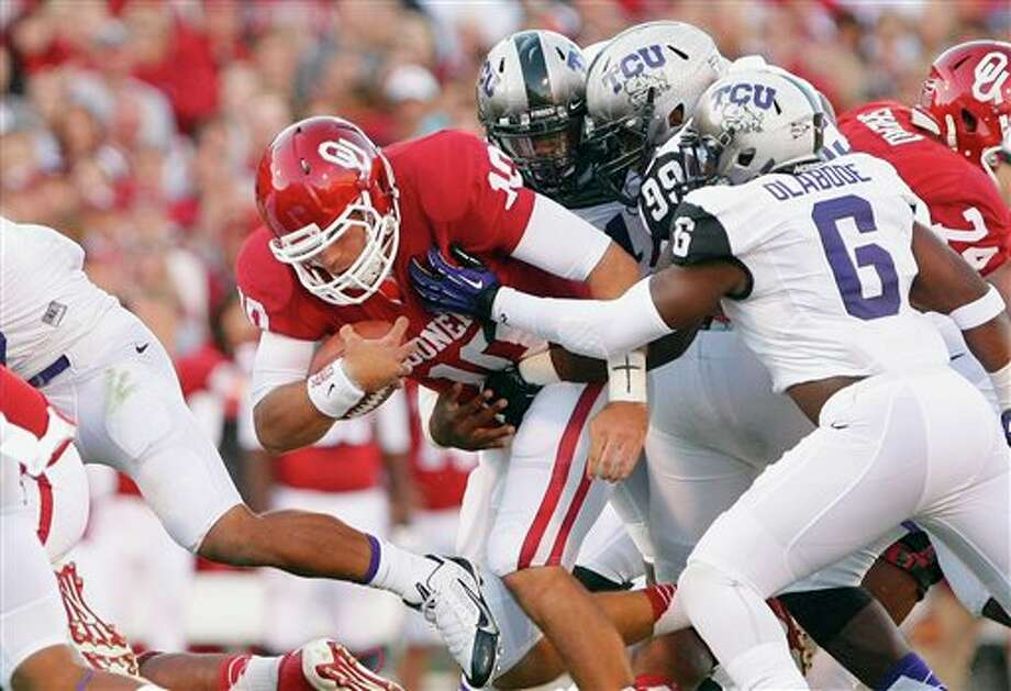 Oklahoma quarterback Blake Bell, center, is tackled by TCU's Elisha Olabode (6) and Tevin Lawson (99) during the first half of an NCAA college football game on Saturday, Oct. 5, 2013, in Norman, Okla. (AP Photo/Alonzo Adams) Photo: Alonzo Adams / FR159426 AP
