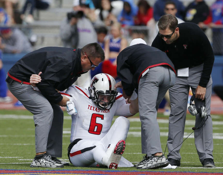 Texas Tech quarterback Baker Mayfield (6) is helped from the field by trainers and coach Kliff Kingsbury, right, during the second half of an NCAA college football game against Kansas in Lawrence, Kan., on Saturday. (AP Photo/Orlin Wagner) Photo: Orlin Wagner