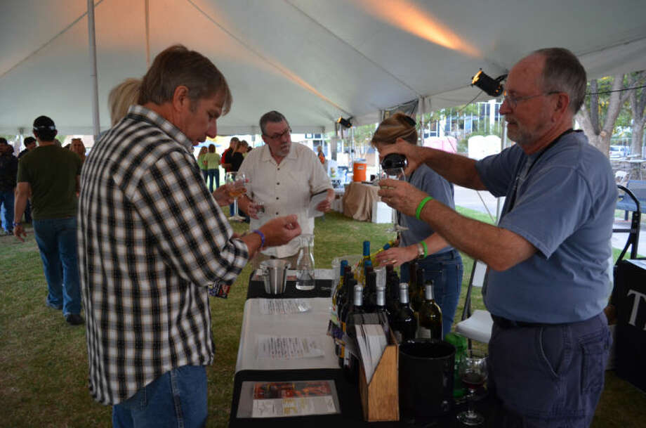 Gary Gilstrap of Texas Hills Vineyard pours his signature tempranillo at the first Food and Wine Festival in downtown Midland Friday. Photo: James Cannon/MRT