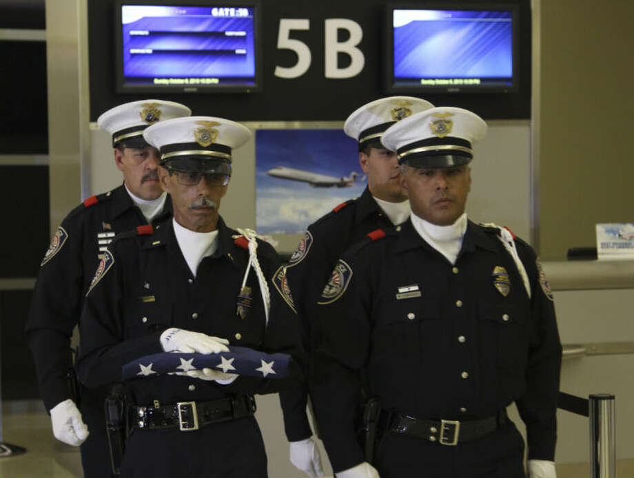 From left to right: MPD Officer Loren Frost, Lt. Victor Rivera, Officer Eluid Amparan and Officer Marcus Dominguez form position to transport the U.S. Honor Flag Sunday night at Midland International Airport. Tyler White/Reporter-Telegram Photo: TYLER WHITE