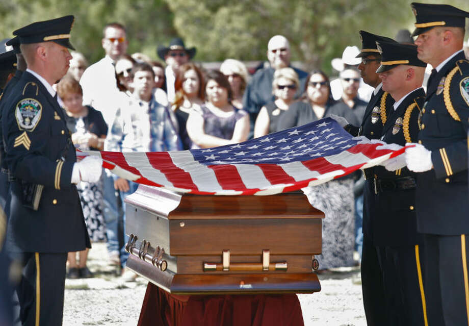 Austin police officers remove the flag from Upton County Sheriff's Deputy Billy Kennedy's casket during the funeral service Tuesday, October 8, 2013 at the Rankin Cemetery in Rankin, Texas. Photo: Ryan Evon|Odessa American