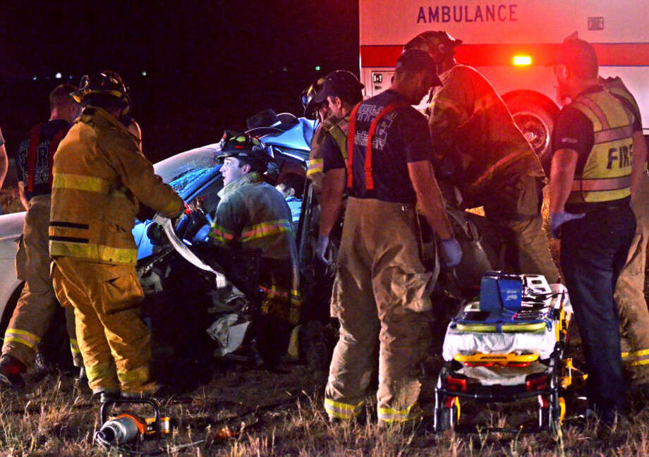 Midland emergency personnel work to extract a man from his vehicle after a two-vehicle collision Tuesday night on Hwy 191. James Durbin/Reporter-Telegram Photo: JAMES DURBIN