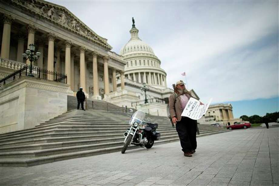 "FILE - In this Oct. 8, 2013, file photo, Rick Hohensee of Washington holds a ""Fire Congress"" sign near the House steps on Capitol Hill in Washington. A new poll says Americans are holding Republicans primarily responsible for the partial government shutdown. The Associated Press-GfK survey finds plenty of disdain to go around as people size up the federal impasse. Most now disapprove of the way President Barack Obama is handling his job, and Congress' approval rating is a perilous 5 percent. (AP Photo/ Evan Vucci) Photo: Evan Vucci / AP"