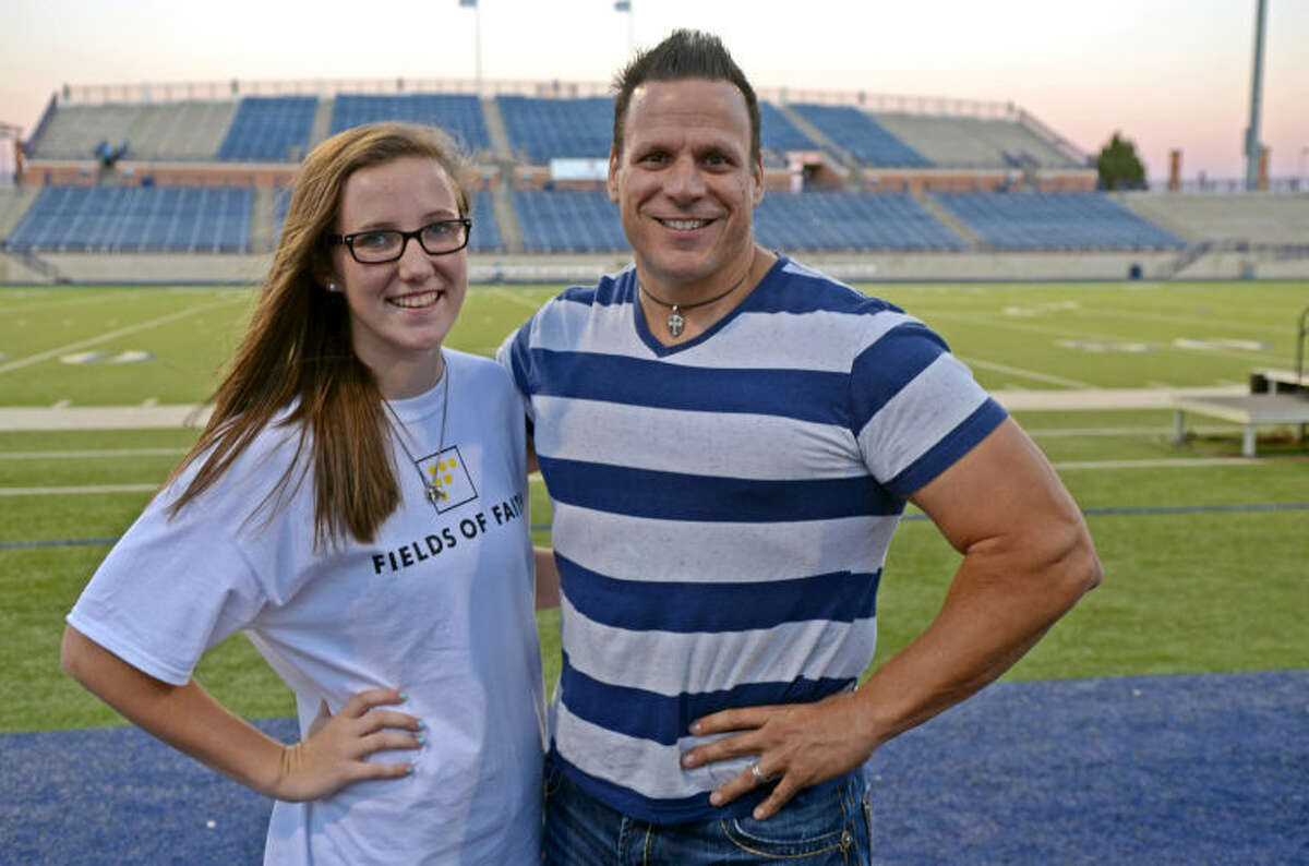 Aubrie Elliott, a junior at Midland High, and Jeff Neal, former guard for the Houston Oilers, pose for a picture before the start of the Fields of Faith event Wednesday at Grande Communications Stadium. James Durbin/Reporter-Telegram