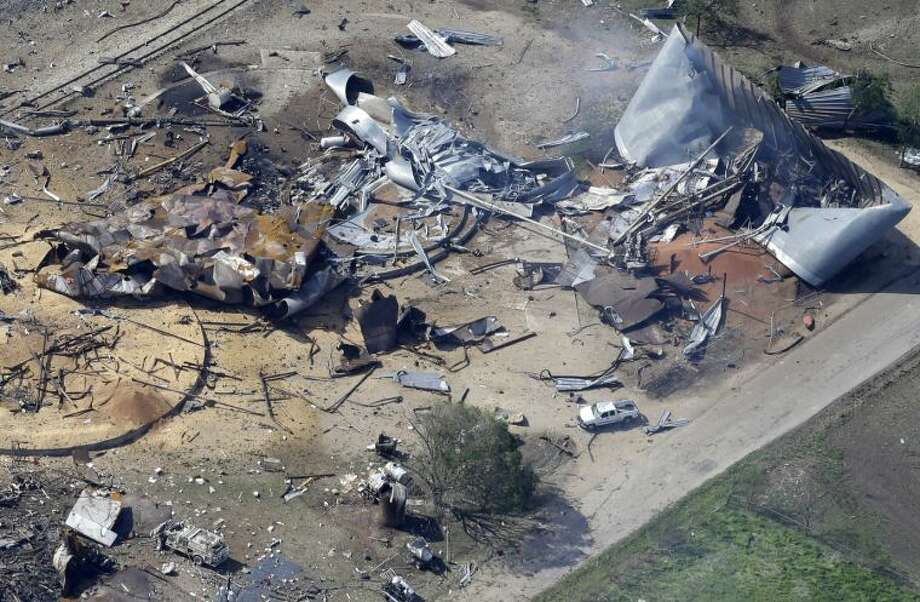 This aerial photo shows the remains of a fertilizer plant destroyed by an explosion and an emergency responders vehicle, bottom left, in West, Texas, Thursday, April 18, 2013. Rescuers searched the smoking remnants for survivors of Wednesday night's thunderous fertilizer plant explosion, gingerly checking smashed houses and apartments for anyone still trapped in debris while the community awaited word on the number of dead. (AP Photo/Tony Gutierrez) Photo: Tony Gutierrez
