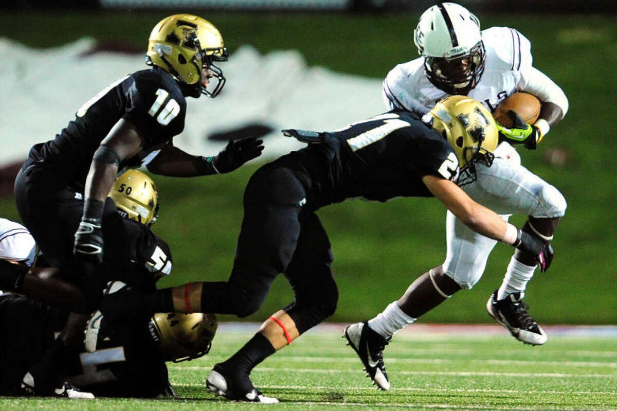 Joy Lewis/Reporter-News Midland Lee's Aron Dobbins (21) escapes Abilene High defensive back Reese Childress (21) during the second half of their game Friday, October 11, 2013 at Shotwell Stadium.