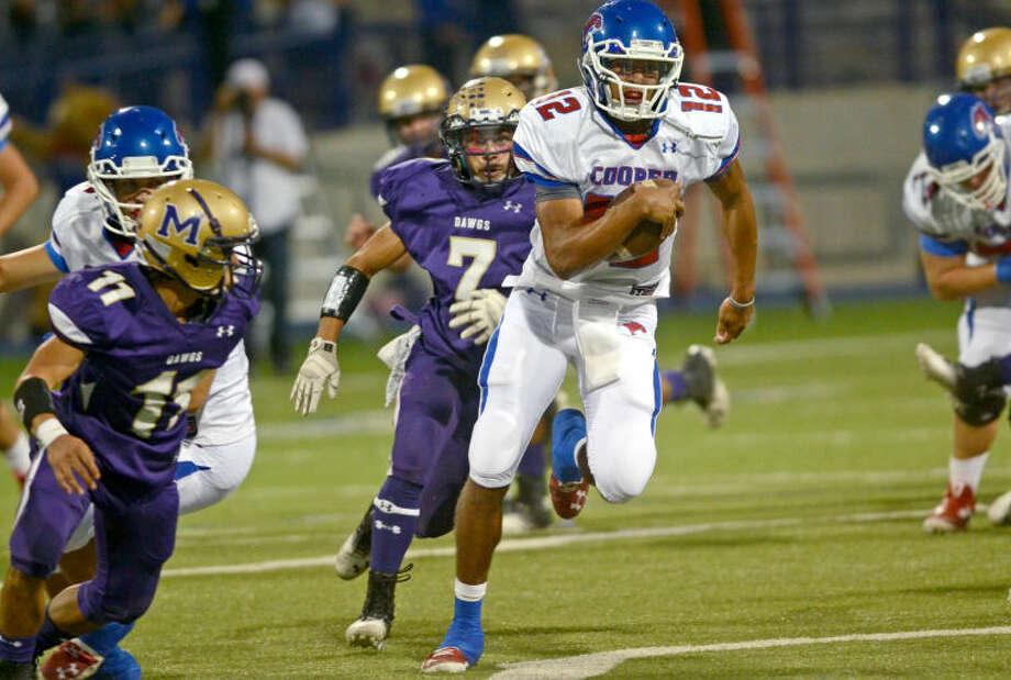 Abilene Cooper quarterback Lorenzo Joe runs past Midland High's Nick Venegas (11) and Xzavier Martinez (7) on Friday at Grande Communications Stadium. James Durbin/Reporter-Telegram Photo: JAMES DURBIN