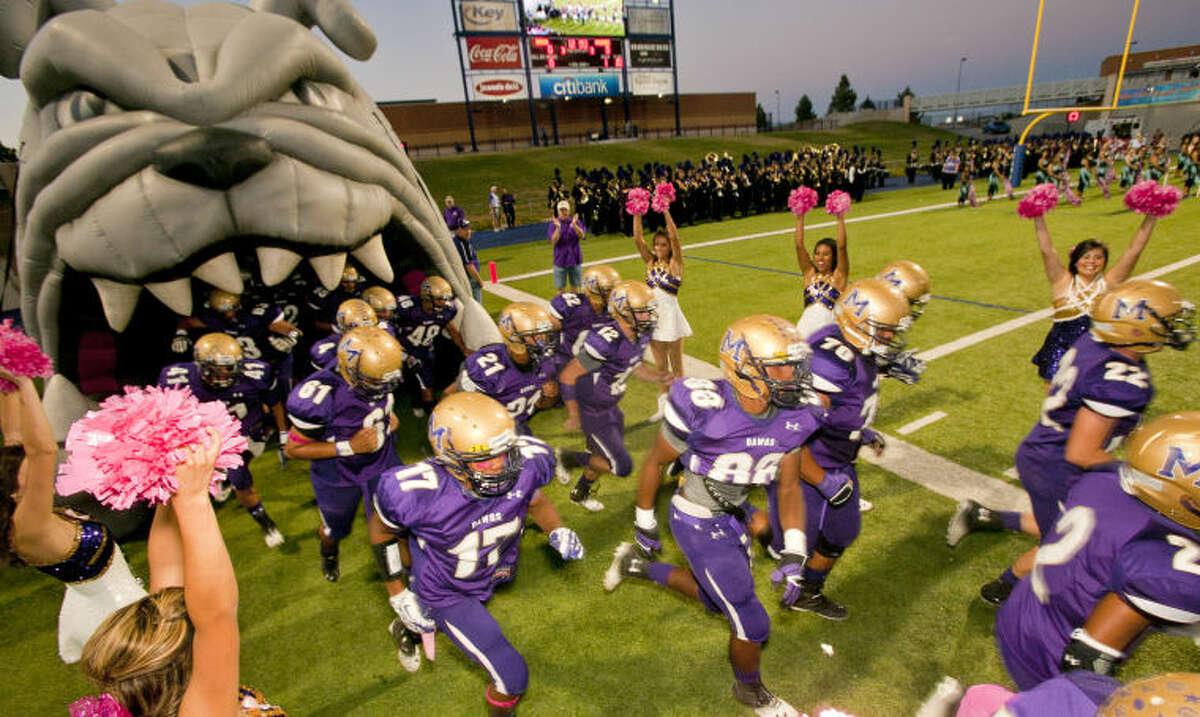 The Midland High football team runs onto the field before the start of the game against Abilene Cooper on Friday at Grande Communications Stadium. James Durbin/Reporter-Telegram