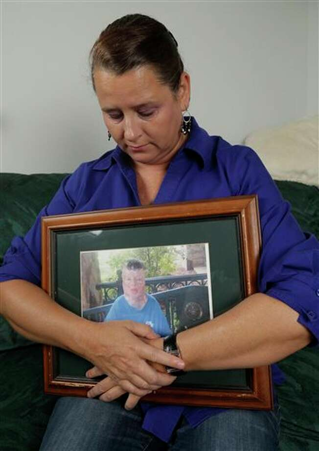 Colleen Middleton holds a photograph of her son, Robert, after an interview in Galveston, Texas on Thursday, Sept. 26, 2013. Robert was severely burned on his eighth birthday after being doused with gasoline, living for 13 years after the incident, but dying from skin cancer in 2011. A murder charge was filed Monday, Sept. 16, 2013, against suspect Don Willburn Collins, 28, who was 13 at the time of the burning. (AP Photo/David J. Phillip) Photo: David J. Phillip / AP