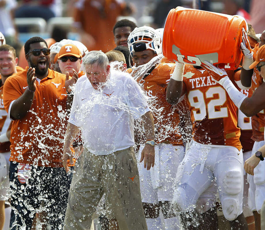 Texas head coach Mack Brown is doused with the water cooler by his players in the closing seconds of their 36-20 win over Oklahoma in an NCAA college football game at the Cotton Bowl in Dallas, Saturday, Oct. 12, 2013. (AP Photo/The Dallas Morning News, Tom Fox) Photo: Tom Fox