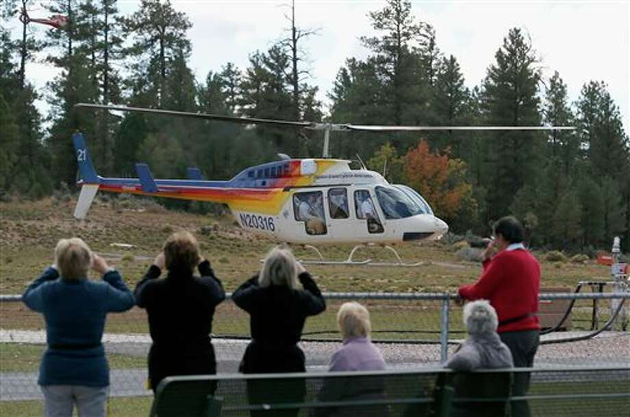 Hundreds of tourists flock to Grand Canyon Airport to take helicopter and plane tours as the only way they could see the Grand Canyon as the entrance to Grand Canyon National Park remains closed to visitors due to the continued federal government shutdown on Friday Oct. 11, 2013, in Tusayan, Ariz. (AP Photo/Ross D. Franklin) Photo: Ross D. Franklin / AP