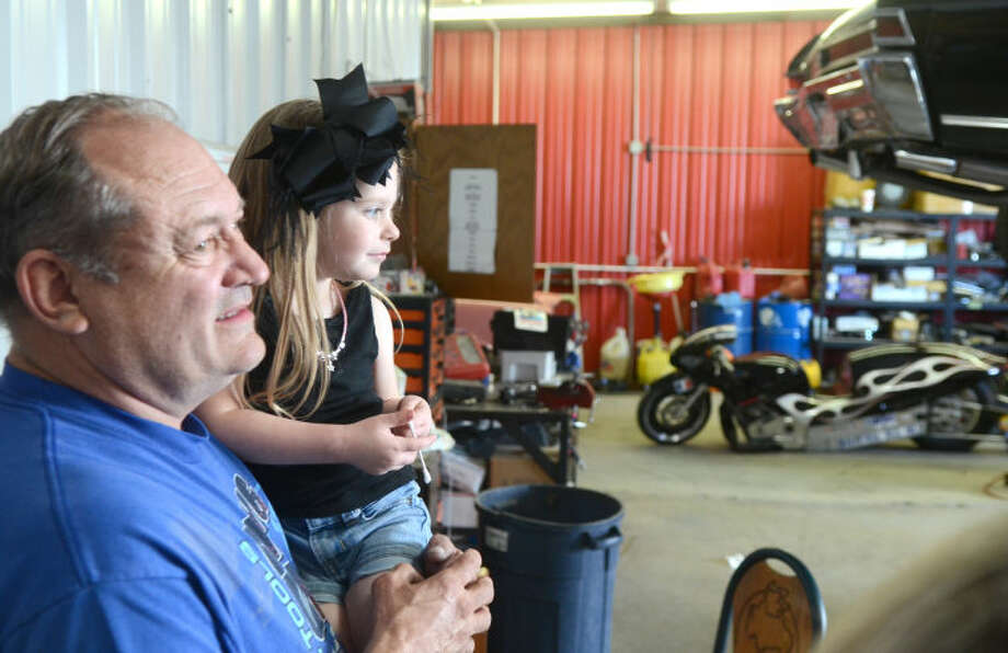 Clayton Hale holds his granddaughter Paisley Hale at Hale's House of Speed on Tuesday. James Durbin/Reporter-Telegram Photo: JAMES DURBIN