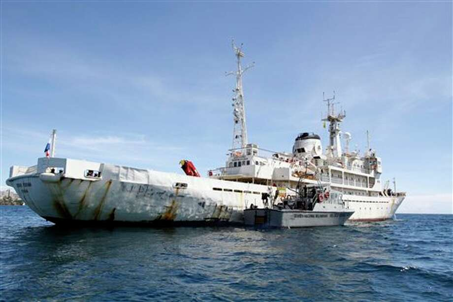 A Venezuelan Coast Guard boat sits next to the 285-foot survey ship Teknik Perdana docked near the shore in Margarita Island, Venezuela, Sunday Oct. 13, 2013. The U.S.-chartered oil exploration ship seized by the Venezuelan navy in Caribbean waters disputed with neighboring Guyana arrived at Venezuela's Margarita Island on Sunday. Venezuelan authorities said the ship's 36 crew members, including five U.S. citizens and two Brazilians, would be held on board while an investigation continued. (AP Photo/Gustavo Granado) Photo: Gustavo Granado / AP