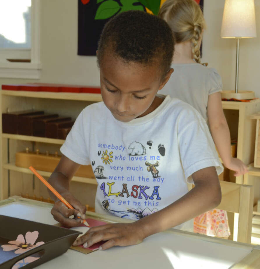 David Mugoya works on drawing as Cora McKean, behind, picks out a new activity Tuesday at Young Bossom Montessori School. Tim Fischer\Reporter-Telegram Photo: Tim Fischer