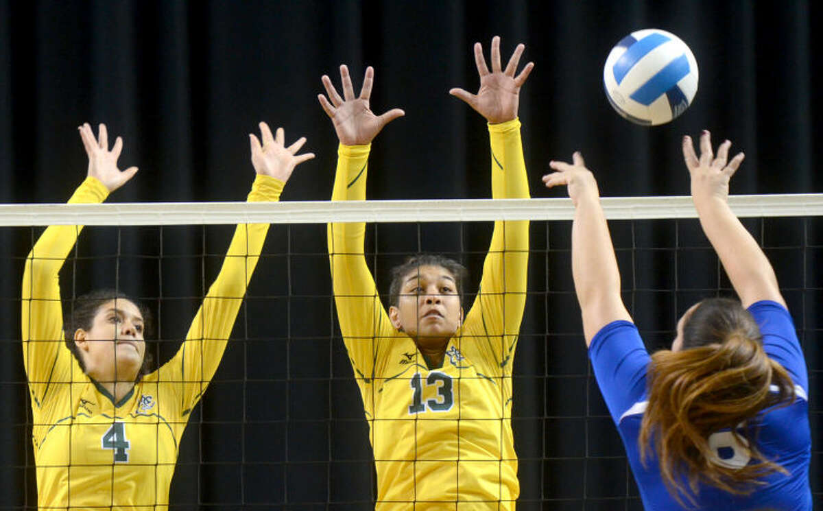 Midland College's Gaby Nieto (4) and Larissa Gomes (13) try to block a hit from Odessa College's Carlie Tuiasosopo Wednesday at Chaparral Center. James Durbin/Reporter-Telegram