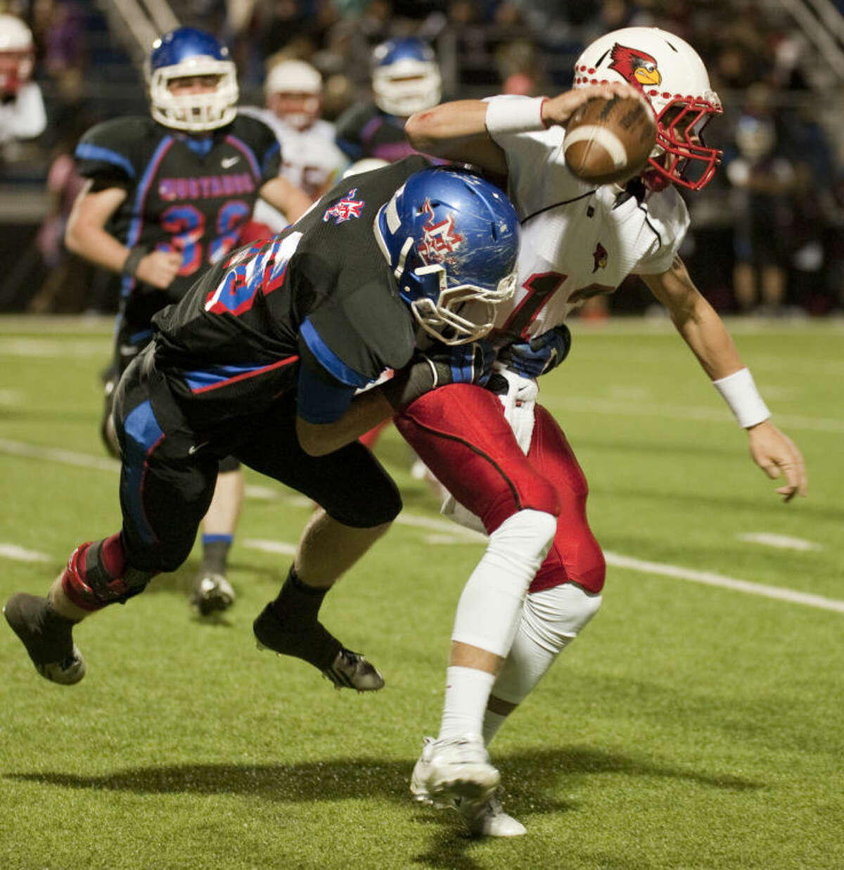 Midland Christian's Reid Talley holds on to bring down Fort Worth Christian's Blaze Brownlow on Friday at Mustang Field. Tim Fischer\Reporter-Telegram