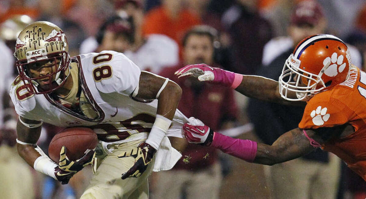 Florida State wide receiver Rashad Greene (80) tries to escape the grasp of Clemson defensive back Bashaud Breeland (17) during the first half of an NCAA college football game, Saturday, Oct. 19, 2013, in Clemson, S.C. (AP Photo/Mike Stewart)