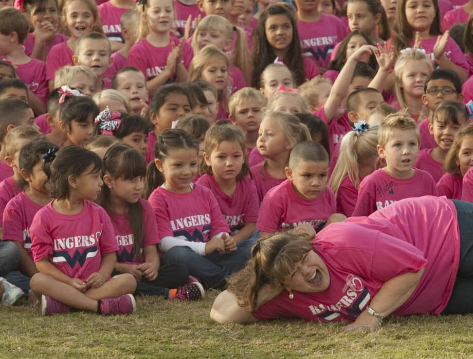 Christine Wiginton laughs as she poses in front as Greenwood Elementary students all wore pink shirts Friday for a picture on the football field to honor Wiginton and all other breast cancer survivors. Tim Fischer\Reporter-Telegram Photo: Tim Fischer