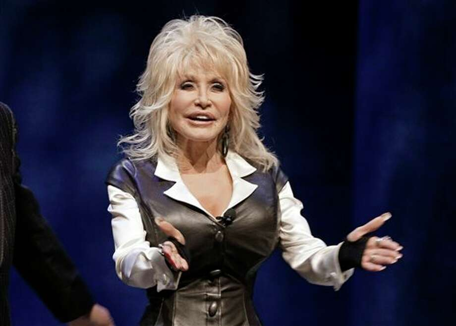 FILE - This Jan. 19, 2012 file photo shows entertainer Dolly Parton during a news conference in Nashville, Tenn., to announce plans for a water-snow park. Parton was treated and released at a Nashville, Tenn., hospital Monday, Oct. 21, 2013, after a car she was riding in was involved in an accident. (AP Photo/Mark Humphrey, File) Photo: Mark Humphrey / AP