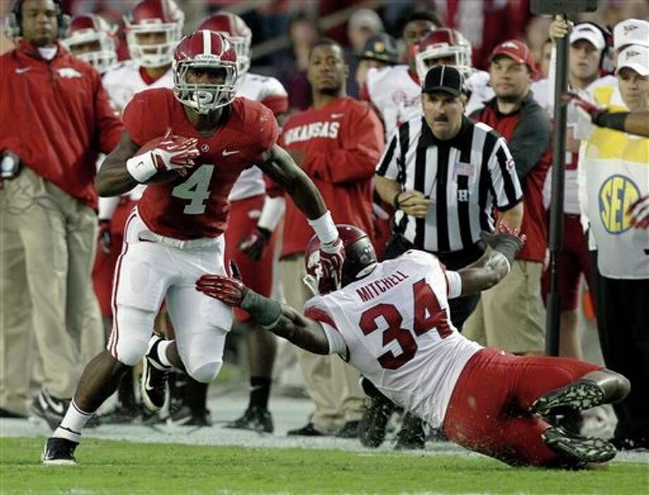 Alabama running back T.J. Yeldon (4) gets around Arkansas linebacker Braylon Mitchell (34) and picks up a first down during the first half of an NCAA college football game on Saturday, Oct. 19, 2013, in Tuscaloosa, Ala. (AP Photo/Butch Dill) Photo: Butch Dill / FR111446 AP