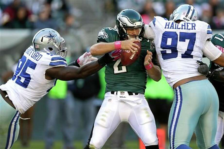 Philadelphia Eagles quarterback Matt Barkley, center, is pressured by Dallas Cowboys defensive end Caesar Rayford, left, and defensive tackle Jason Hatcher, right, during the second half of an NFL football game, Sunday, Oct. 20, 2013, in Philadelphia. The Cowboys won 17-3. (AP Photo/Matt Rourke) Photo: Matt Rourke / AP