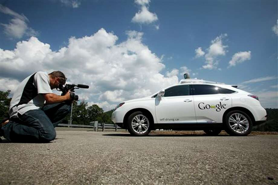 ,FILE -This Sept. 3, 2013, file photo shows a videographer photographing the Google self-driving car during a news conference at the Virginia Tech Transportation Institute's Smart Road in Blacksburg Va. A new study that attempts to quantify the benefits of self-driving cars and trucks says they hold the potential to transform driving by eliminating the majority of traffic deaths, significantly reducing congestion and providing tens of billions of dollars in economic benefits. (AP Photo / The Roanoke Times, Matt Gentry, File) Photo: Matt Gentry / The Roanoke Times