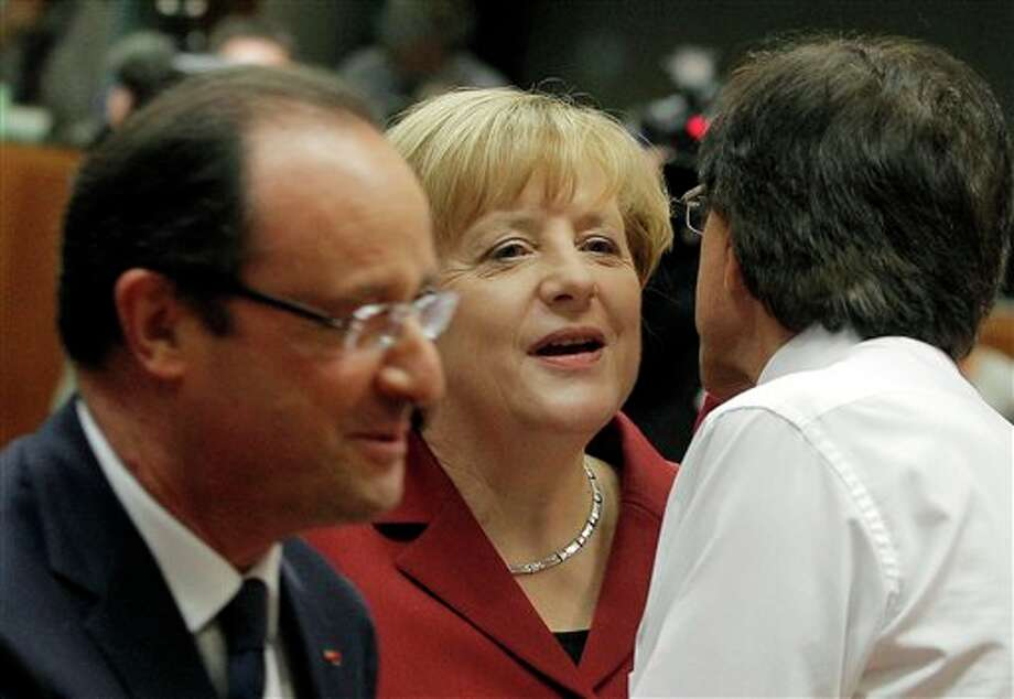 German Chancellor Angela Merkel, center, is greeted by Belgian Prime Minister Elio Di Rupo, right, as French President Francois Hollande, left, walks by during a round table meeting at an EU summit in Brussels, Thursday, Oct. 24, 2013. A two-day summit meeting of EU leaders is likely to be diverted from its official agenda, economic recovery and migration, after German Chancellor Angela Merkel complained to U.S. President Barack Obama that U.S. intelligence may have monitored her mobile phone. (AP Photo/Yves Logghe) Photo: Yves Logghe / AP
