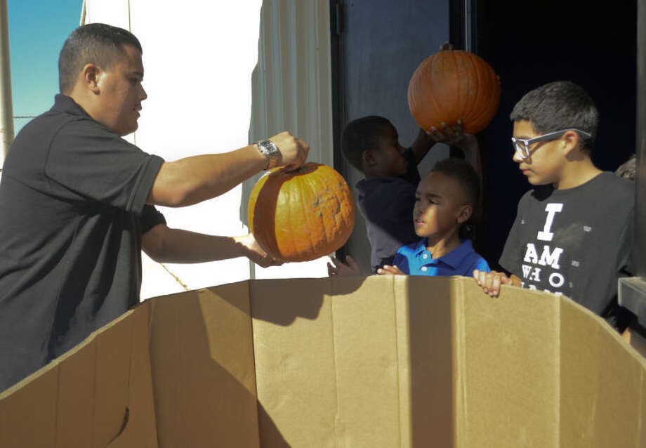 Michael Jasso, former Boys and Girls Club participant, is now Boys and Girls Club unit director in Midland gets help unloading a crate of pumpkins at the center. Tim Fischer\Reporter-Telegram Photo: Tim Fischer