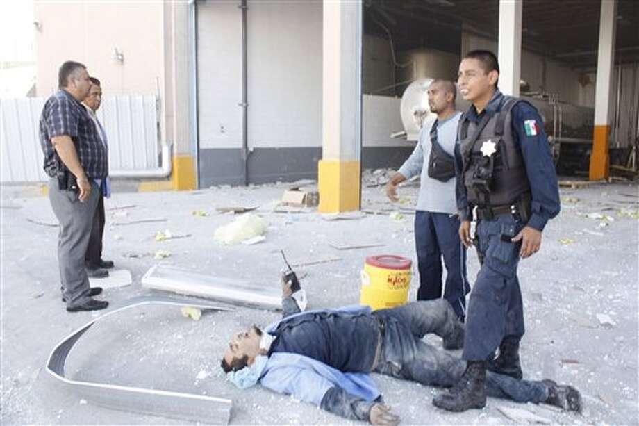 Socorristas ayudan a un hombre que resultó herido por una explosión en una fábrica de dulces en Ciudad Juárez, México, el jueves 24 de octubre de 2013. La explosión en la fábrica Dulces Blueberry hizo que el piso se colapsara, dejando al menos 40 heridos. (Foto AP/Raymundo Ruiz) Photo: Raymundo Ruiz / AP