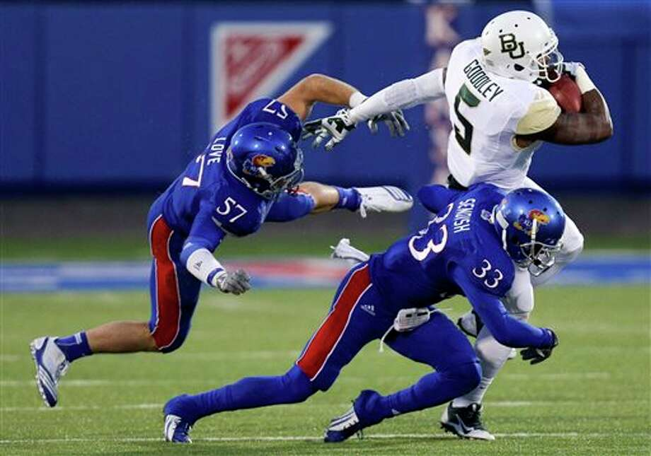 Baylor Bears wide receiver Antwan Goodley catches a pass against Kansas Jayhawks linebacker Jake Love (57) and Cassius Sendish (33) in the first quarter of an NCAA college football game Saturday, Oct. 26, 2013, in Lawrence, Kan. (AP Photo/Ed Zurga) Photo: Ed Zurga / FR34145 AP